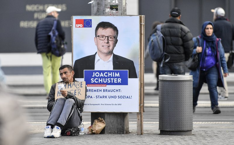 In this Tuesday, May 14, 2019 photo, a man with a sign reading 'I am hungry' begs in front of a poster showing SPD candidate Joachim Schuster for the European Elections in the center of Bremen, Germany. The city became a battleground for EU's fragile political center, support for Germany's Social Democrats has ebbed dramatically in recent years, but nowhere is their fate more closely watched than in the tiny city-state of Bremen. (AP Photo/Martin Meissner)