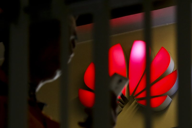 A man looks at his smartphone past a Huawei retail shop is seen through a handrail inside a commercial office building in Beijing, Tuesday, May 21, 2019. The Trump administration's sanctions against Huawei have begun to bite even though their dimensions remain unclear. U.S. companies that supply the Chinese tech powerhouse with computer chips saw their stock prices slump Monday, and Huawei faces decimated smartphone sales with the anticipated loss of Google's popular software and services. (AP Photo/Andy Wong)