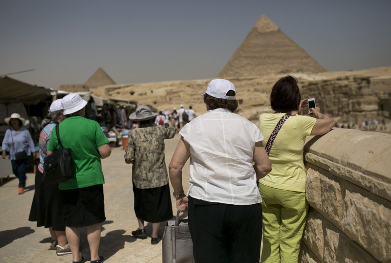 Tourists visit the Giza Pyramids near Cairo, Egypt, Tuesday, May 21, 2019, two days after a tour bus struck an improvised explosive device near the site, wounding more than a dozen foreign tourists. (AP Photo/Maya Alleruzzo)