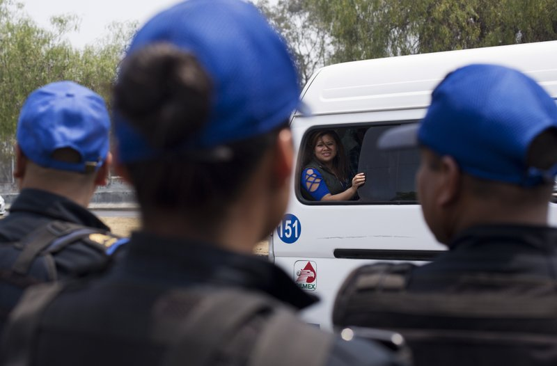 In this May 15, 2019 photo, a woman in a public transport van looks toward police who are part of a program in which officers ride buses in pairs to protect passengers and drivers from armed robbery in the Iztapalapa borough of Mexico City. There were an average of 70 reported violent muggings every day in Mexico City in the first four months of 2019, and between 2017 and 2018, such assaults rose by about 22%. (AP Photo/Rebecca Blackwell)