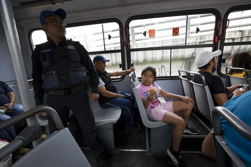 In this May 15, 2019 photo, a young passenger sits near police officer Jose Osorio del Angel who stands at the back of the bus, in the Iztapalapa borough of Mexico City. The government of the eastern borough launched a program this week to have police ride the buses to prevent robberies. (AP Photo/Rebecca Blackwell)