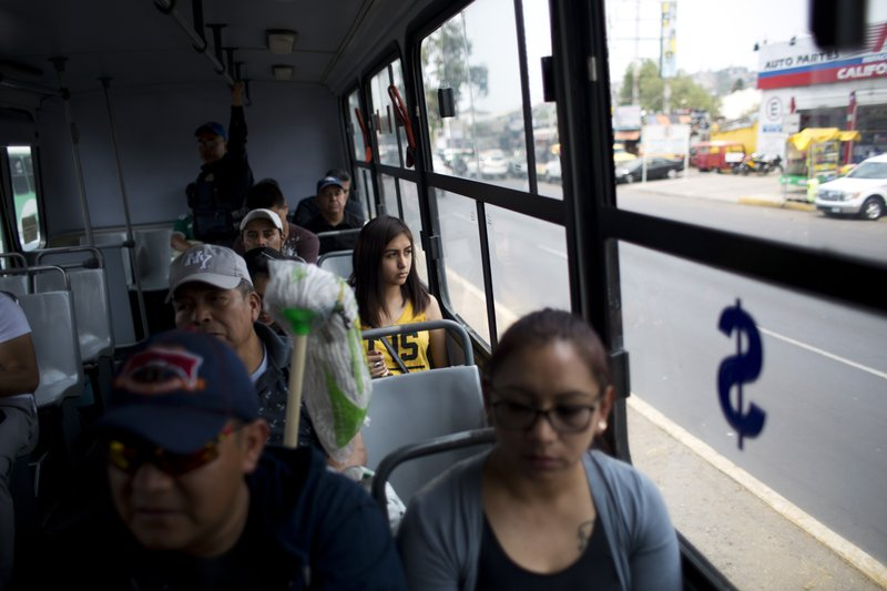 In this May 15, 2019 photo, passengers ride a public bus as police officer Jose Osorio del Angel stands watch from the back in the Iztapalapa borough of Mexico City. The government of the eastern borough of Ixtapalpa launched a program this week to have police ride the buses to prevent robberies. (AP Photo/Rebecca Blackwell)