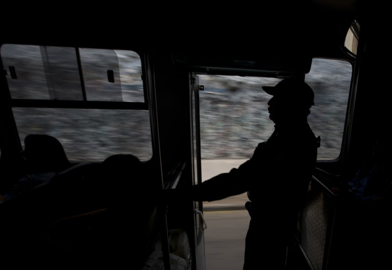 In this May 15, 2019 photo, police officer Gilberto Ramos Rodriguez stands watch at the back door of a public bus in the Iztapalapa borough of Mexico City. The government of the eastern borough of Ixtapalpa launched a program this week to have police ride the buses to prevent robberies. (AP Photo/Rebecca Blackwell)