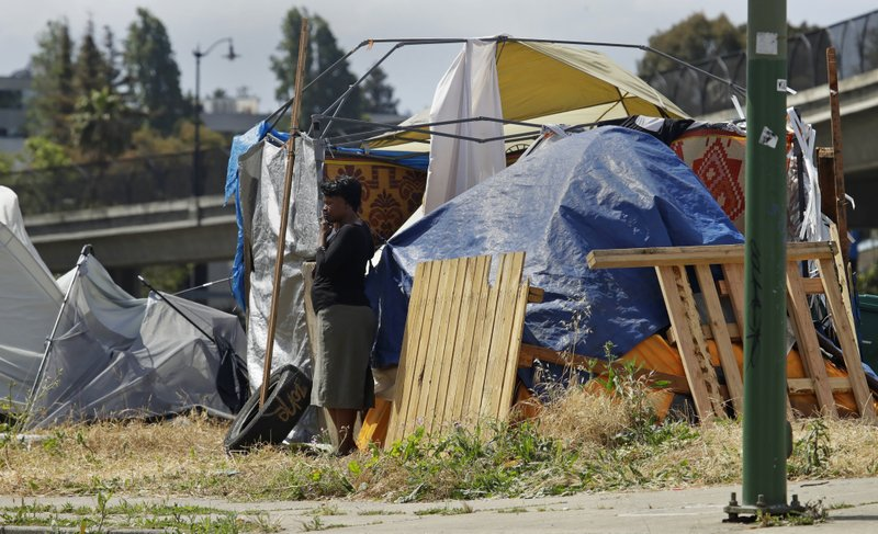 In this photo taken on Friday, May 17, 2019, a woman smokes a cigarette outside a homeless encampment in Oakland, Calif. California Gov. Gavin Newsom is creating a task force on homelessness as the state grapples with a housing crisis. Speaking Tuesday, May 21,  in Oakland, Newsom described homelessness as an epidemic of statewide concern but says it will be best addressed at the local level. (AP Photo/Ben Margot, File)