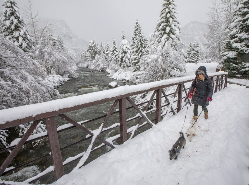 Frisco resident Dianne Stuhr walks with her dogs, Winston and Patty, Tuesday, May 21, 2019, along Tenmile Creek in Frisco, Colo. Nearby Breckenridge Ski Resort reported 9 inches of snow overnight. (Hugh Carey/Summit Daily News via AP)
