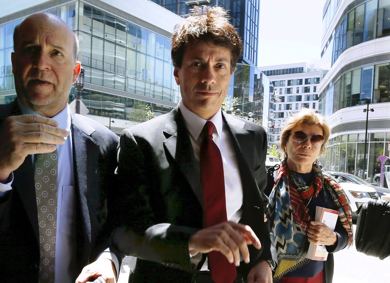 Agustin Huneeus, center, arrives at federal court Tuesday, May 21, 2019, in Boston, where he is scheduled to plead guilty to charges in a nationwide college admissions bribery scandal. (AP Photo/Michael Dwyer)
