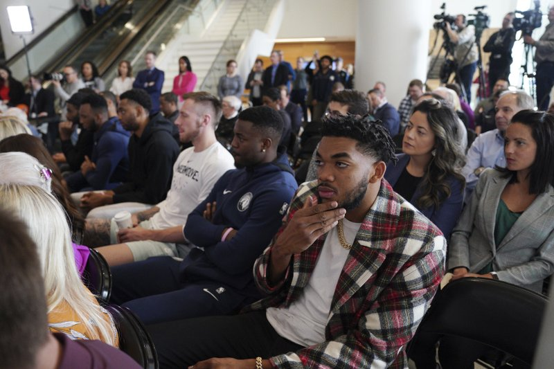 Minnesota Timberwolves center Karl-Anthony Towns, foreground, listens at a press conference where Ryan Saunders was introduced as the NBA basketball team's new head coach in Minneapolis, Tuesday, May 21, 2019. (Anthony Souffle/Star Tribune via AP)