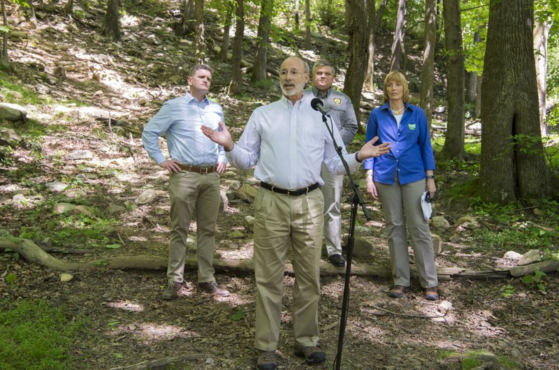 Pennsylvania Governor Tom Wolf talks to the press at the base of the Falls Trail at Glen Onoko Falls in Jim Thorpe, Pa., Tuesday, May 21, 2019. Pennsylvania Senator John T. Yudichak, Pennsylvania Game Commission Executive Director Bryan Burhans and DCNR Secretary Cindy Adams Dunn, back, were also on hand to field questions regarding the trails closure earlier this month. State officials say the hiking trail will remain closed to the public unless lawmakers pass Gov. Tom Wolf's $4.5 billion infrastructure plan.   (Bob Ford/Erie Times-News via AP)