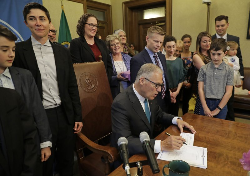 Katrina Spade, upper left, the founder and CEO of Recompose, a company that hopes to use composting as an alternative to burying or cremating human remains, looks on Tuesday, May 21, 2019, as Washington Gov. Jay Inslee, center, signs a bill into law at the Capitol in Olympia, Wash., that allows licensed facilities to offer