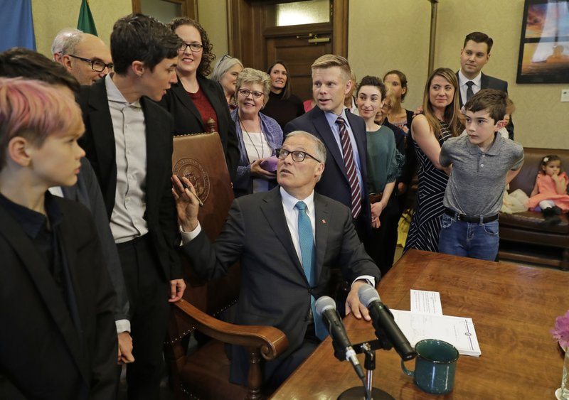 Washington Gov. Jay Inslee, center, turns to talk with Katrina Spade, upper left, the founder and CEO of Recompose, a company that hopes to use composting as an alternative to burying or cremating human remains, Tuesday, May 21, 2019, at the Capitol in Olympia, Wash., before signing a bill into law that allows licensed facilities to offer
