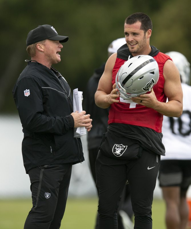 Oakland Raiders NFL football team head coach Jon Gruen, left, confers with his quarterback Derek Carr (4) during an official team activity, Tuesday, May 21, 2019, in Alameda, Calif. (AP Photo/D. Ross Cameron)