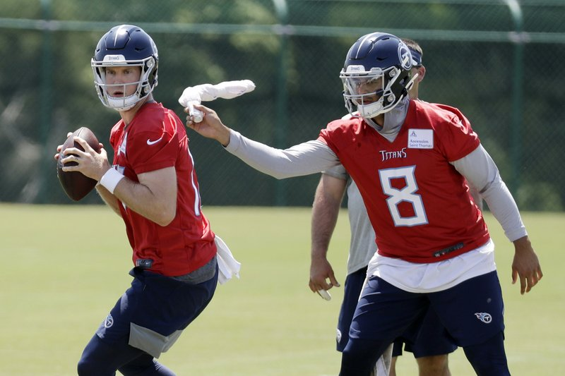 Tennessee Titans quarterback Marcus Mariota (8) swats quarterback Ryan Tannehill (17) during a drill at an organized team activity at the Titans' NFL football training facility Tuesday, May 21, 2019, in Nashville, Tenn. (AP Photo/Mark Humphrey)