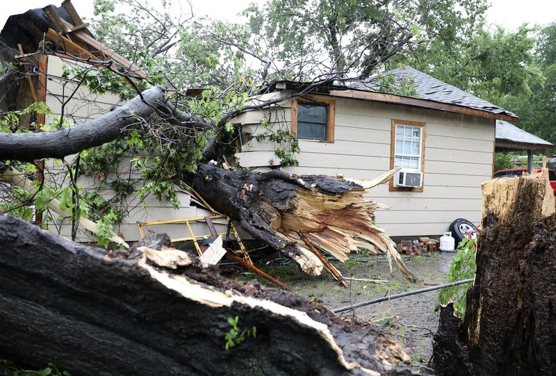 A large tree rests inside a home where a man was rescued near Newton and St. Louis Avenue in Tulsa, Okla., on Tuesday, May 21, 2019. (Tom Gilbert/Tulsa World via AP)