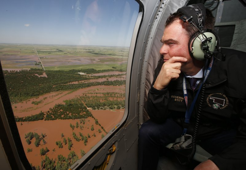Oklahoma Gov. Kevin Stitt surveys flooding damage near Minco, Okla., from the air Tuesday, May 21, 2019, following heavy rains across the state. (AP Photo/Sue Ogrocki)
