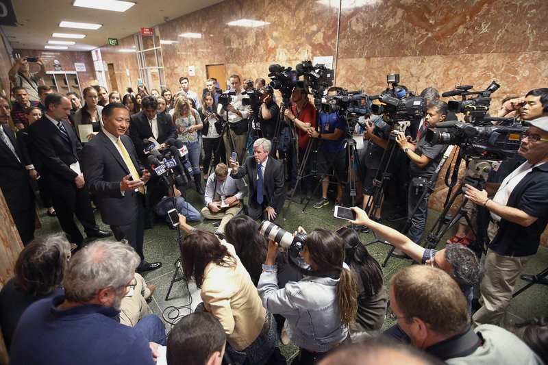 FILE - In this July 7, 2015, file photo, San Francisco Public Defender Jeff Adachi, left, talks to members of the media after Francisco Sanchez' arraignment in San Francisco. Bryan Carmody, a San Francisco reporter, is seeking the return of property after police raided his home with a sledgehammer, as officials sought to determine the source of a leaked police report into Adachi's death. An attorney for Carmody will make the request Tuesday, May 21, 2019, in San Francisco County Superior Court. (AP Photo/Tony Avelar, File)