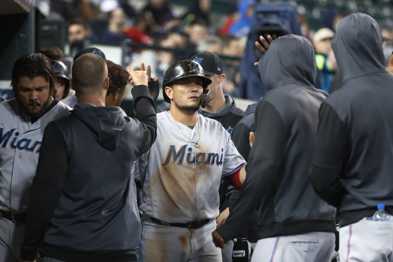 Miami Marlins' Miguel Rojas celebrates scoring on a Chad Wallach double during the 11th inning of the team's baseball game against the Detroit Tigers in Detroit, Tuesday, May 21, 2019. (AP Photo/Paul Sancya)