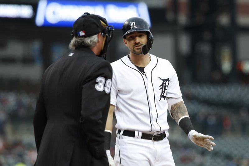 Detroit Tigers' Nicholas Castellanos, right, talks with home plate umpire Paul Nauert after striking out against the Miami Marlins during the first inning of a baseball game in Detroit, Tuesday, May 21, 2019. (AP Photo/Paul Sancya)