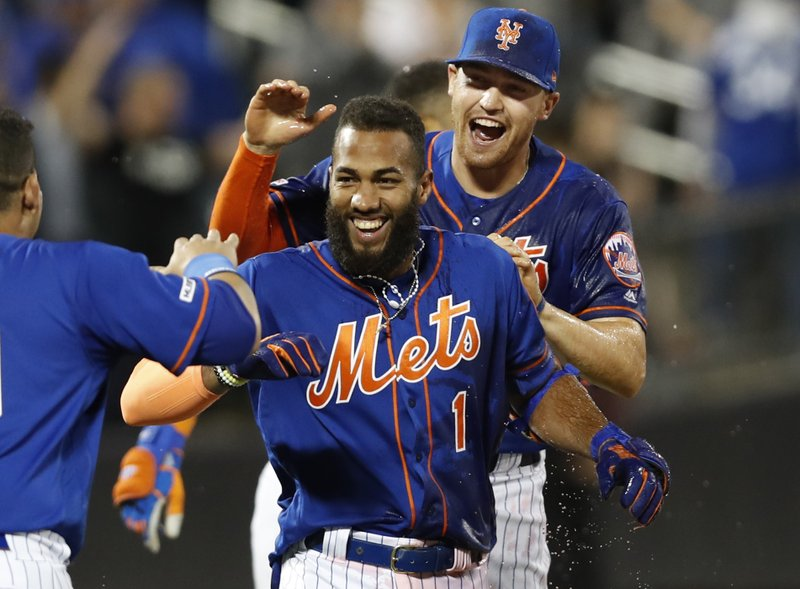 New York Mets Brandon Nimmo, right, celebrates with the Mets Amed Rosario (1) after Rosario hit a walk-off, RBI single during the ninth inning of a baseball game against the Washington Nationals, Tuesday, May 21, 2019, in New York. (AP Photo/Kathy Willens)
