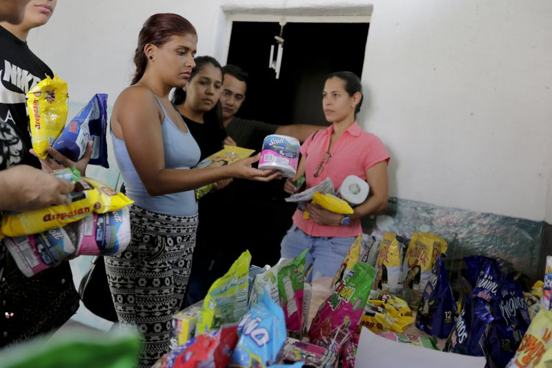 In this April 11, 2019 photo, customers choose groceries that will be paid using cryptocurrency in Barquisimeto, Venezuela, Thursday, April 11, 2019. Storing cryptocurrency presents greater financial risks than holding U.S. dollars though, due to the wild swings in the value of some crypto assets, including bitcoin. But in Venezuela, where the local currency has lost two thirds of its value this year, some merchants are willing to give this technology a shot. (AP Photo/Manuel Rueda)