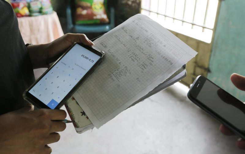 In this April 11, 2019 photo, Leticia Luque calculates the exchange rate of cryptocurrency, in Barquisimeto, Venezuela, Thursday, April 11, 2019. Luque, an informal merchant, said that she began to accept crypto payments two months ago at the request of a social worker. (AP Photo/Manuel Rueda)