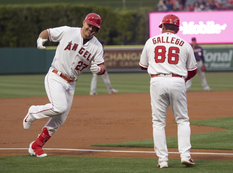Los Angeles Angels' Mike Trout, left, celebrates his solo home run with third base coach Mike Gallego during the first inning of a baseball game against the Minnesota Twins in Anaheim, Calif., Tuesday, May 21, 2019. (AP Photo/Kyusung Gong)