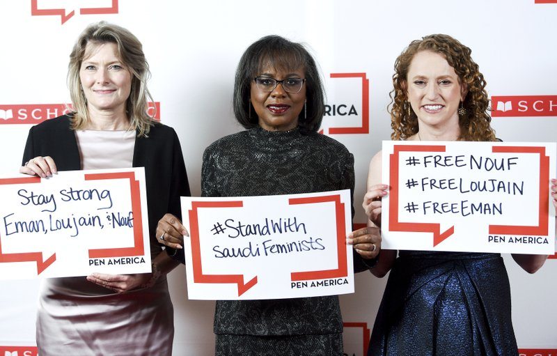 PEN America president Jennifer Egan, left, PEN courage award recipient Anita Hill and PEN America CEO Suzanne Nossel pose together holding signs in support of jailed Saudi women's rights activists Nouf Abdulaziz, Loujain Al-Hathloul and Eman Al-Nafjan at the 2019 PEN America Literary Gala at the American Museum of Natural History on Tuesday, May 21, 2019, in New York. (Photo by Evan Agostini/Invision/AP)