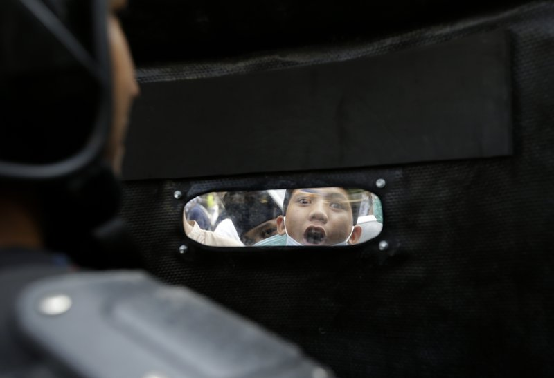 A protester shouts slogans as he is seen through the shield of a riot police officer in Jakarta, Indonesia, Wednesday, May 22, 2019. Supporters of an unsuccessful presidential candidate clashed with security forces in the Indonesian capital on Wednesday, burning vehicles and throwing rocks at police using tear gas and rubber bullets. (AP Photo/Dita Alangkara)
