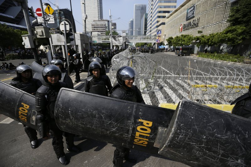 Riot police officers take their position outside the building that house the Election Supervision Board in Jakarta, Indonesia, Wednesday, May 22, 2019. Supporters of an unsuccessful presidential candidate clashed with security forces in the Indonesian capital on Wednesday, burning vehicles and throwing rocks at police using tear gas and rubber bullets. (AP Photo/Dita Alangkara)
