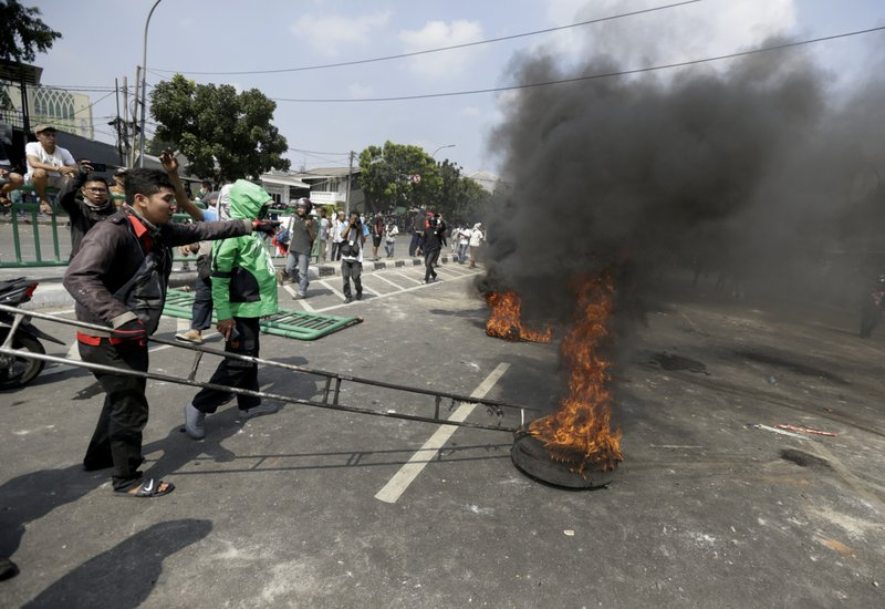 Protesters burn tires on a street during a clash with the police in Jakarta, Indonesia, Wednesday, May 22, 2019. Supporters of an unsuccessful presidential candidate clashed with security forces in the Indonesian capital on Wednesday, burning vehicles and throwing rocks at police using tear gas and rubber bullets. (AP Photo/Dita Alangkara)
