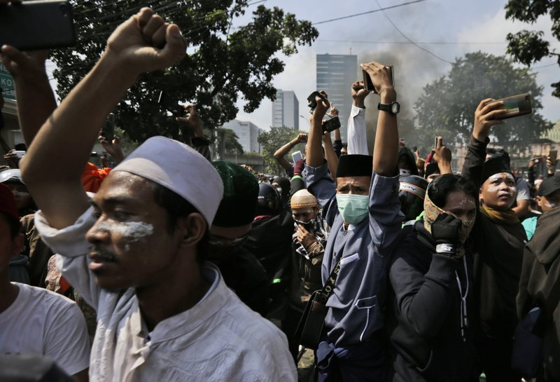 Protesters raise their fists as they taunt officers during a clash with the police in Jakarta, Indonesia, Wednesday, May 22, 2019. Supporters of an unsuccessful presidential candidate clashed with security forces in the Indonesian capital on Wednesday, burning vehicles and throwing rocks at police using tear gas and rubber bullets. (AP Photo/Dita Alangkara)