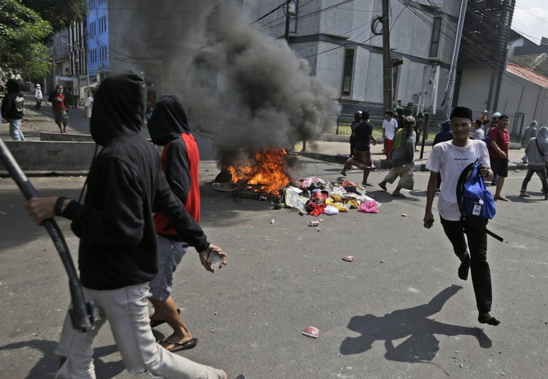 Protesters walk past burning garbage during a clash with the police in Jakarta, Indonesia, Wednesday, May 22, 2019. Supporters of an unsuccessful presidential candidate clashed with security forces in the Indonesian capital on Wednesday, burning vehicles and throwing rocks at police using tear gas and rubber bullets. (AP Photo/Dita Alangkara)
