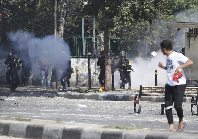 Indonesian riot police officers fire a tear gas launcher to disperse supporters of Indonesian presidential candidate Prabowo Subianto in Jakarta, Indonesia, Wednesday, May 22, 2019. Supporters of the unsuccessful presidential candidate clashed with security forces and set fire to a police dormitory and vehicles in the Indonesian capital on Wednesday after the release of official election results. (AP Photo/Achmad Ibrahim)