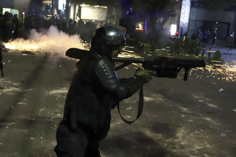 An Indonesian riot police officer fires a tear gas launcher to disperse supporters of Indonesian presidential candidate Prabowo Subianto in Jakarta, Indonesia, early Wednesday, May 22, 2019. Supporters of the unsuccessful presidential candidate clashed with security forces and set fire to a police dormitory and vehicles in the Indonesian capital on Wednesday after the release of official election results. (AP Photo)