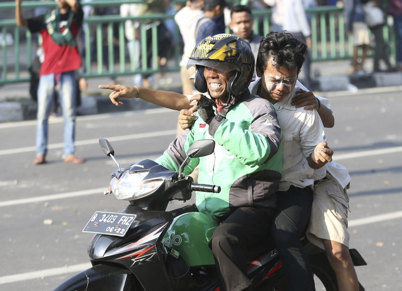 A Grab bike driver rides carries an injured supporter of Indonesian presidential candidate Prabowo Subianto during a clash with Indonesian police in Jakarta, Indonesia, Wednesday, May 22, 2019. Supporters of the unsuccessful presidential candidate clashed with security forces and set fire to a police dormitory and vehicles in the Indonesian capital on Wednesday after the release of official election results. (AP Photo/Achmad Ibrahim)