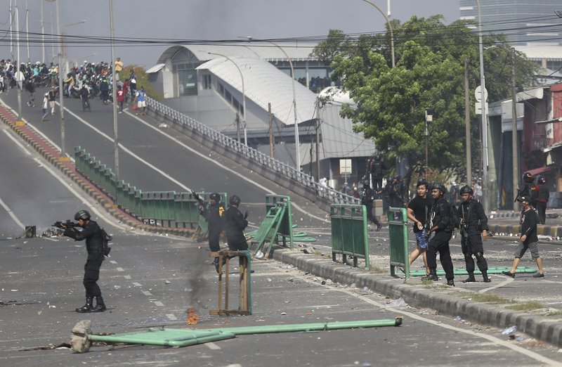 Indonesian police take position during a clash with supporters of Indonesian presidential candidate Prabowo Subianto in Jakarta, Indonesia, Wednesday, May 22, 2019. Supporters of the unsuccessful presidential candidate clashed with security forces and set fire to a police dormitory and vehicles in the Indonesian capital on Wednesday after the release of official election results. (AP Photo/Achmad Ibrahim)