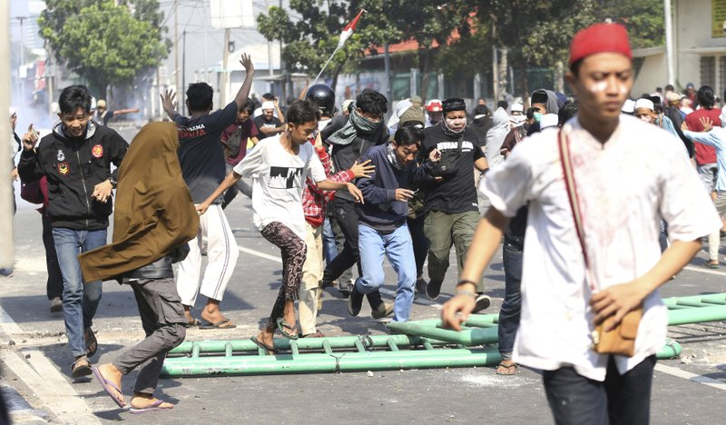 Supporters of Indonesian presidential candidate Prabowo Subianto run during a clash with the police in Jakarta, Indonesia, Wednesday, May 22, 2019. Supporters of the unsuccessful presidential candidate clashed with security forces and set fire to a police dormitory and vehicles in the Indonesian capital on Wednesday after the release of official election results.(AP Photo/Achmad Ibrahim)