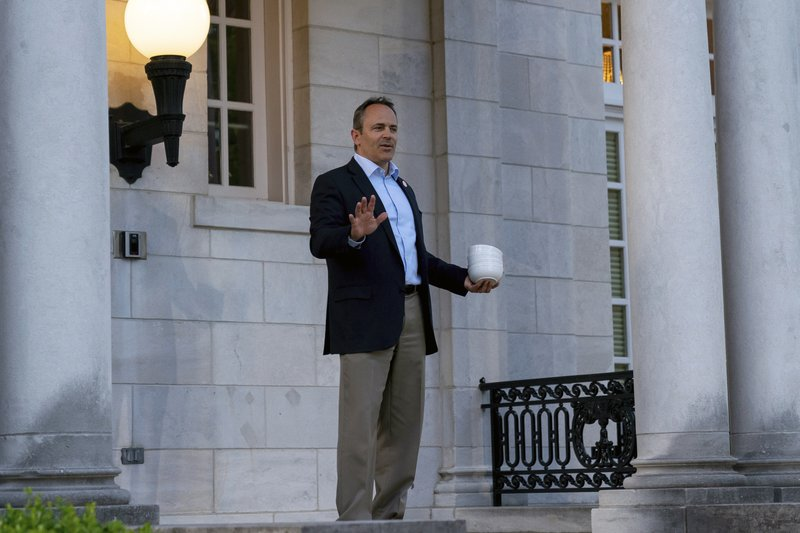 Kentucky Gov. Matt Bevin arrives at his election night news conference carrying bowls, offering the media chili, after winning the Republican gubernatorial primary, in Frankfort, Ky., Tuesday, May 21, 2019. (AP Photo/Bryan Woolston)