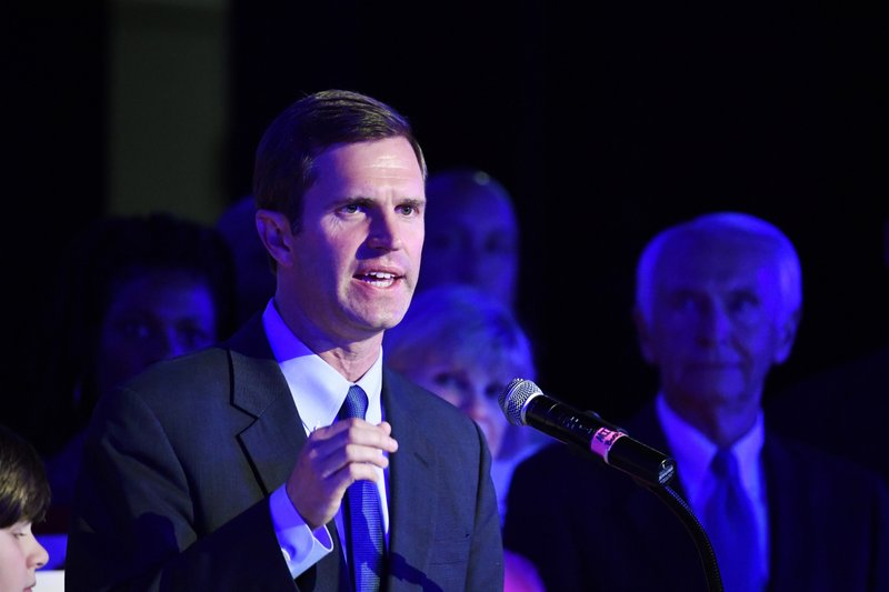 Kentucky Attorney General Andy Beshear, left, addresses his supporters following his victory in the democratic primary for Governor in Louisville, Ky., Tuesday, May 21, 2019. Right is his father and former Kentucky Gov. Steve Beshear. (AP Photo/Timothy D. Easley)