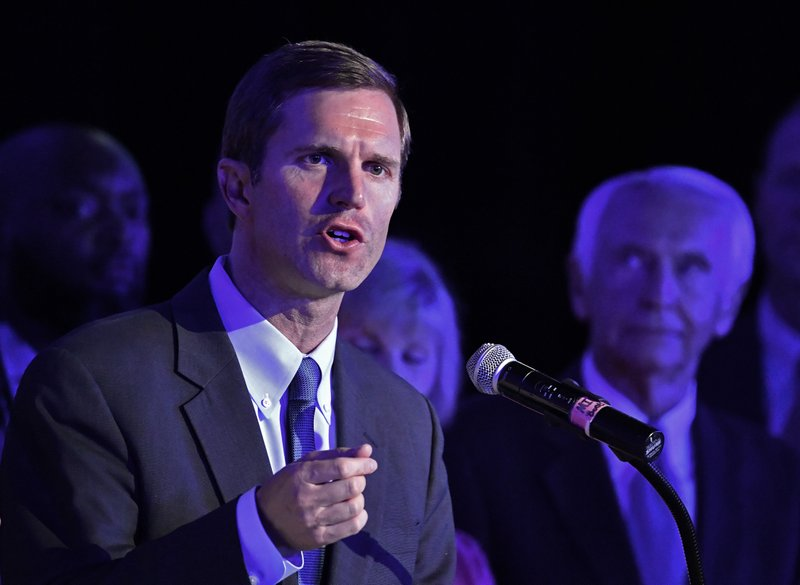 CORRECTS DATE TO TUESDAY, MAY 21 - Kentucky Attorney General Andy Beshear, left, addresses his supporters following his victory in the democratic primary for Governor in Louisville, Ky., Tuesday, May 21, 2019. Right is his father and former Kentucky Gov. Steve Beshear. (AP Photo/Timothy D. Easley)