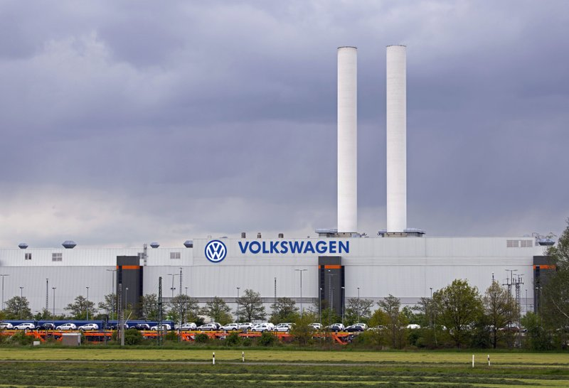 In this Tuesday, May 14, 2019 photo a train loaded with cars stand in front of the plant of the German manufacturer Volkswagen AG (VW) in Zwickau, Germany. Volkswagen will total shift into electric cars at the plant in Zwickau and the first vehicles are to roll off the assembly line at the end of 2019. (AP Photo/Jens Meyer)