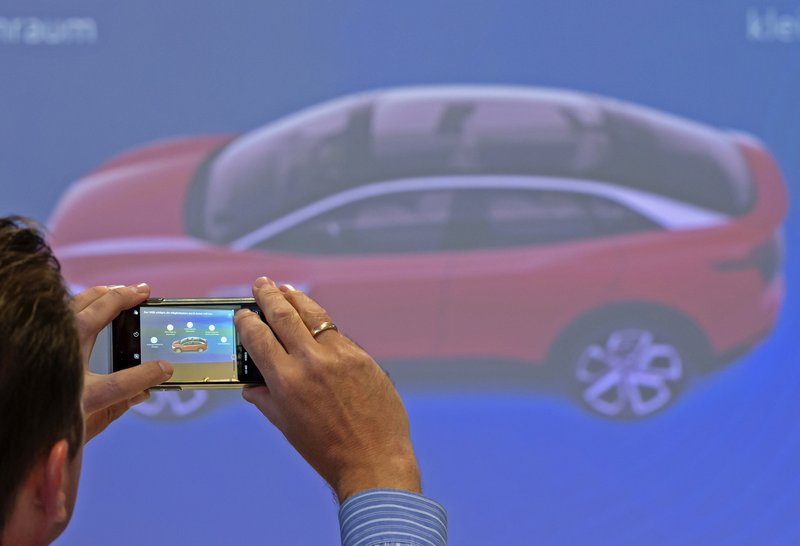 In this Tuesday, May 14, 2019 photo, a journalists shoots photos during a presentation of details to the new electric 'ID.3' car at a press tour of the plant of the German manufacturer Volkswagen AG (VW) in Zwickau, Germany. Volkswagen will total shift into electric cars at the plant in Zwickau and the first vehicles are to roll off the assembly line at the end of 2019. (AP Photo/Jens Meyer)