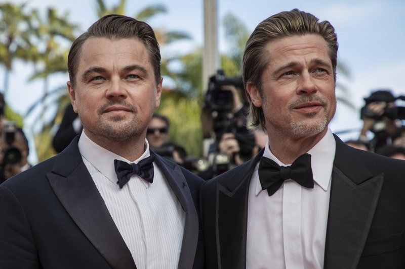 Actors Leonardo DiCaprio, left, and Brad Pitt pose for photographers at the premiere of their film