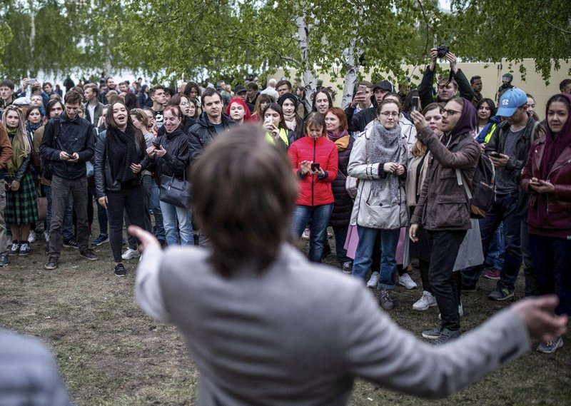 An orator speaks to a crowd at a fence to block demonstrators protesting plans to construct a cathedral in a park in Yekaterinburg, Russia, Thursday, May 16, 2019. (AP Photo/Evgeny Feldman)
