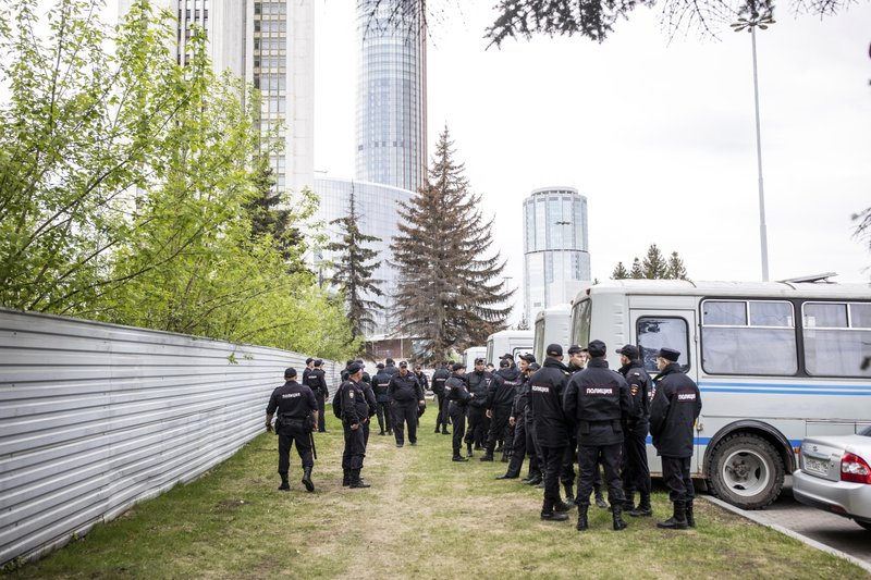 Police officers stand in front of a fence to block demonstrators protesting plans to construct a cathedral in a park in Yekaterinburg, Russia, Thursday, May 16, 2019. Russian police detained several dozen people in the early hours on Thursday at a rally protesting plans to build a cathedral in a popular park in Russia's fourth-largest city. (AP Photo/Evgeny Feldman)