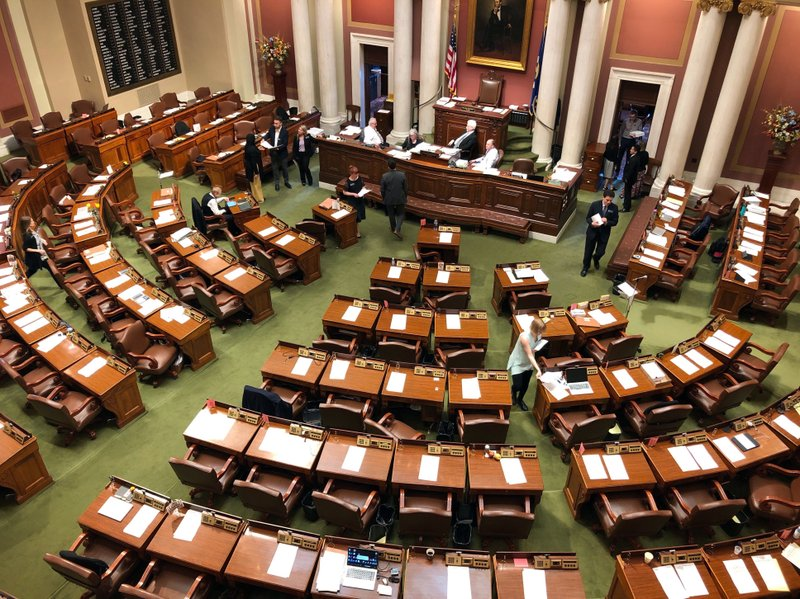 The Minnesota House chamber at the state Capitol in St. Paul sits mostly empty Thursday, May 16, 2019, in St. Paul, Minn., as leaders work behind the scenes to try wrap up a budget deal in hopes of avoiding a stalemate that could require a special session. (AP Photo/Steve Karnowski)