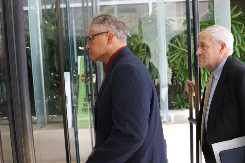 Former Honolulu police chief Louis Kealoha, left, walks into federal court in Honolulu on Wednesday, May 22, 2019. A trial for what has been described as the biggest corruption case in Hawaii history began Wednesday for Kealoha and his former city prosecutor wife, Katherine Kealoha. The two are accused of conspiring to frame Katherine Kealoha's uncle for a crime he did not commit. The Kealoha's were indicted on charges including conspiracy and obstruction. Federal authorities began investigating the two in 2015 and both stepped down from their jobs as the probe deepened. (AP Photo/Caleb Jones)