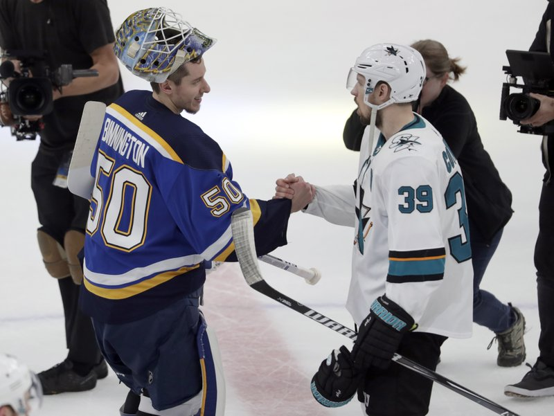 St. Louis Blues goaltender Jordan Binnington (50) and San Jose Sharks' Logan Couture (39) shake hands following Game 6 of the NHL hockey Stanley Cup Western Conference final series Tuesday, May 21, 2019, in St. Louis. The Blues won the game 5-1 to take the series 4-2. (AP Photo/Tom Gannam)