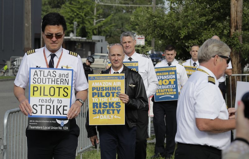 Pilots demonstrating for better working conditions people who fly planes for Amazon.com and Atlas Air Worldwide picket outside Amazon.com's annual shareholders meeting, Wednesday, May 22, 2019, in Seattle. (AP Photo/Ted S. Warren)