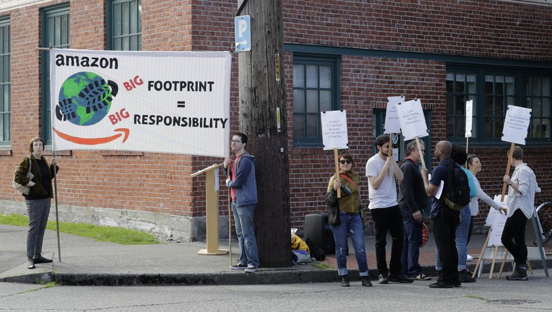 People asking Amazon.com to take a stronger role in fighting climate change and environmental issues, demonstrate outside Amazon.com's annual shareholders meeting, Wednesday, May 22, 2019, in Seattle. (AP Photo/Ted S. Warren)