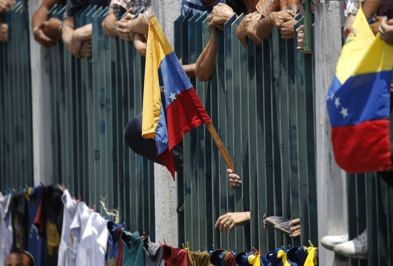A supporter of Venezuela's opposition leader and self-proclaimed interim president Juan Guaidó gholds a national flag at a rally in Guatire, Venezuela, Saturday, May 18, 2019. (AP Photo/Ariana Cubillos)